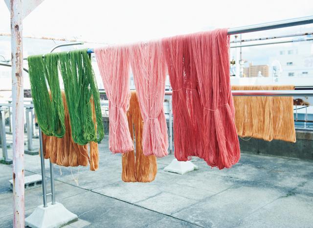 画像: 何度も色を重ねて染め上げた木綿糸は、アトリエの屋上に並べて干す。これは芯の周りに巻く地巻き色。1カセで直径24cmの手まり約20個分になる