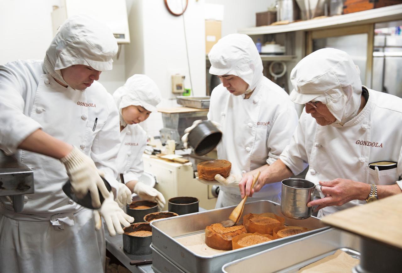 画像: 焼き上がったパウンドケーキを、スタッフ総出で仕上げる。最後のラム酒をぬる作業は、進さんの役目。この作業が、しっとりした食感につながっている