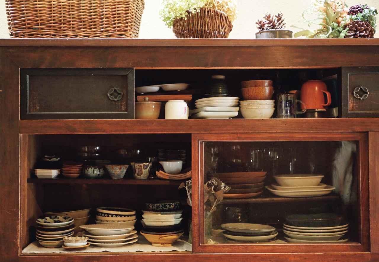 画像: よく使う食器は、一番取り出しやすいガラス戸の棚に。上部の板戸の中は、歳時の器や料理道具など、使用頻度の低いものを。「食器はこれ以上増えないように、新しく購入したら、使わなくなった器を友人に譲ったりしています」(※トップの写真 2)