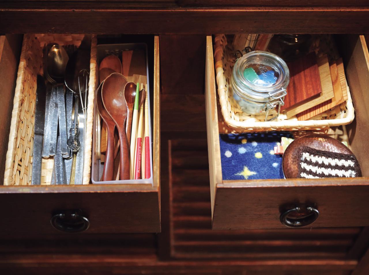 画像: 箸やコースターなど、バラバラになりやすいキッチン雑貨は、水屋箪笥の引き出しに。小ぶりのかごを幾つか並べ、種類ごとに収納している。スプーンも素材で分けているので、見つけやすい(※トップの写真 1)
