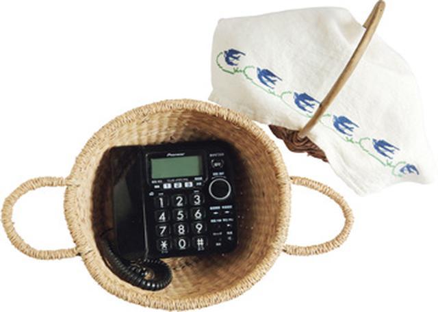 画像: 電話機もかごに入れ、かわいい布をかけて収納。「あわてて買ってしまった電話機の見た目が、ちょっと気に入らなくて。でも、別のものを買うのももったいないので、かごに入れてみました」