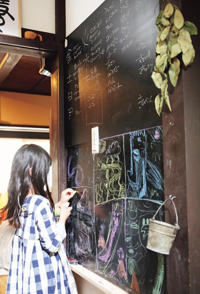 画像: 冷蔵庫の向かいの壁に設置した、お手製の黒板。冷蔵庫の中にある食材や、買い足しするもの、一週間のメニューを、ここにメモしているそう。下半分は、子どもたちのお絵描きスペースに