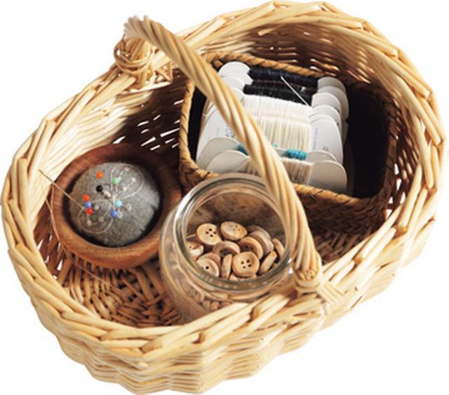 画像: お菓子の詰め合わせが入っていた柳のかごは、再利用して裁縫道具入れに。2階のアトリエで使っているミシンの道具や糸、布なども、大小さまざまなかごに仕分けされ、収納されている