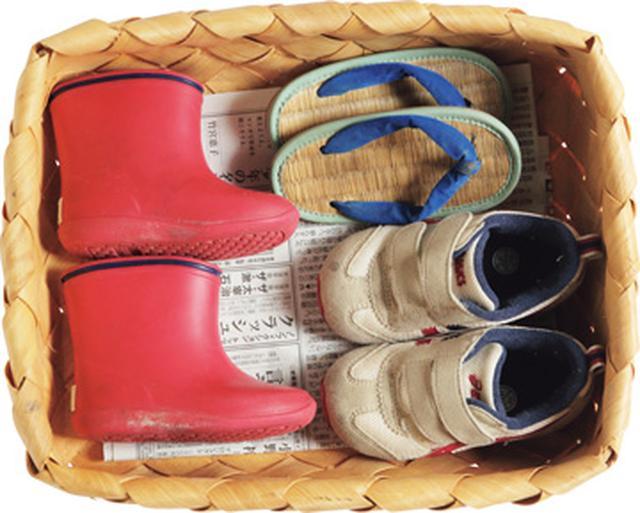 画像: 浅くて大きな柳のかごには、子どもの靴や草履などを収納。靴箱として使っているアジアンテイストの棚の下にかごごと収め、まだ小さなけいくんでも取り出しやすくしている
