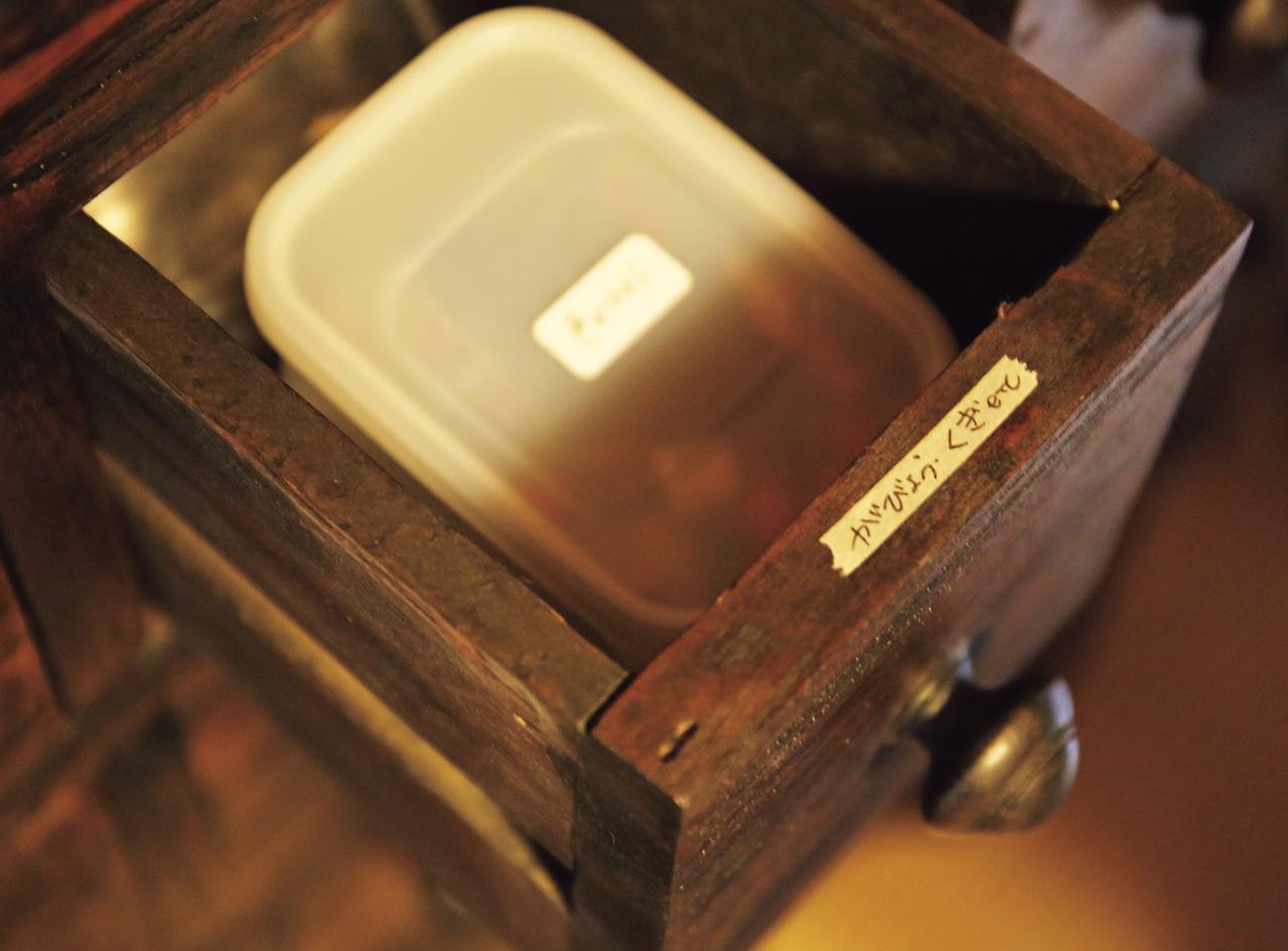 画像: インドネシアの古いチーク材で仕立てた家具は、幾つもある引き出しが便利。文具や薬などを入れているそう。表から見えない場所にマスキングテープのメモを貼り、仕分けしやすい工夫も
