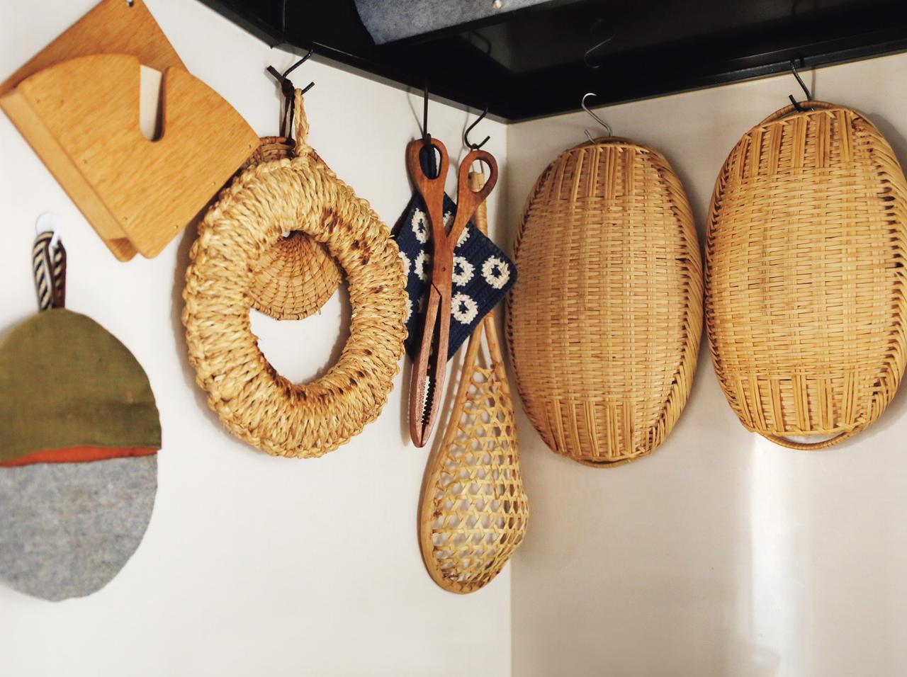 画像: 使用頻度の高いかごやざるは、コンロの上に吊るして収納。「熱で乾くので、洗って、ざっと水をきったら、フックにかけて吊るしています」。左の鍋つかみは、はぎれを使った美濃羽さんの手づくり(※トップの写真 7)