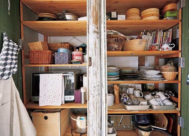 画像: 見た目をきれいにするため、器は素材や色ごとにそろえて収納。トースターなどの電化製品やレシピ本なども、この中に。「収納場所が細かく分かれているより、大きな棚に全部入っているほうが好きなんです」