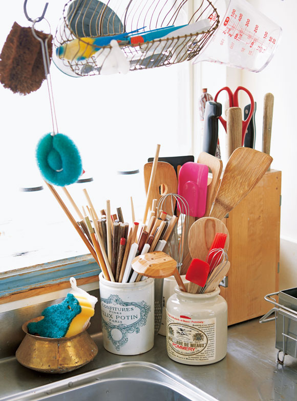 画像: 箸や木べらなどは、引き出しに入れず、お気に入りのマスタードやジャムの空き瓶に。食べ終えたら、捨てずにとっておくそう。タワシやブラシ類は、シンクの上にフックで吊るしている