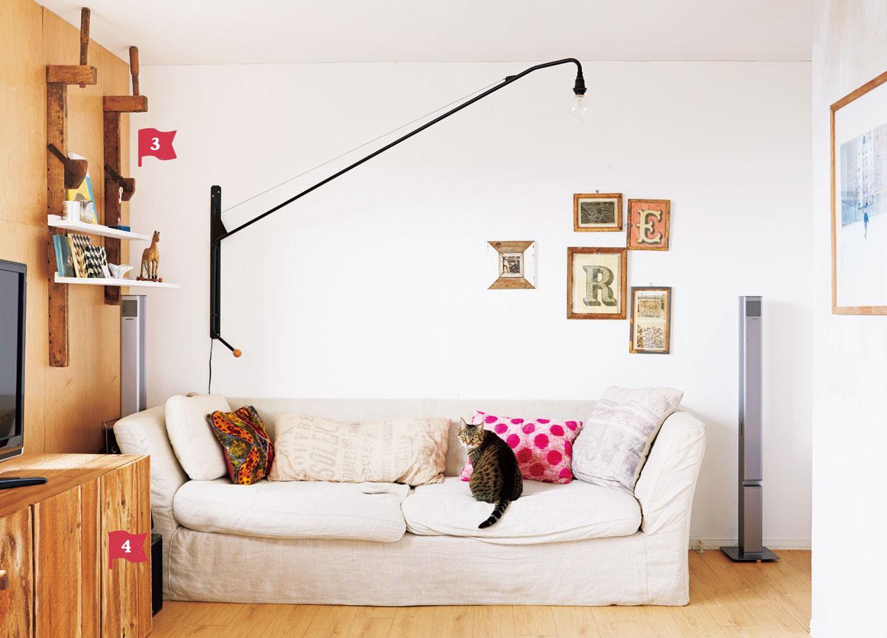画像: リビングのソファは、フランスで購入して、日本に運び込んだもの。壁にはカードやポスターを入れた額縁をリズミカルに並べて。以前は、この壁にも飾り棚を付けていたが、部屋全体のバランスを考えて取り外した