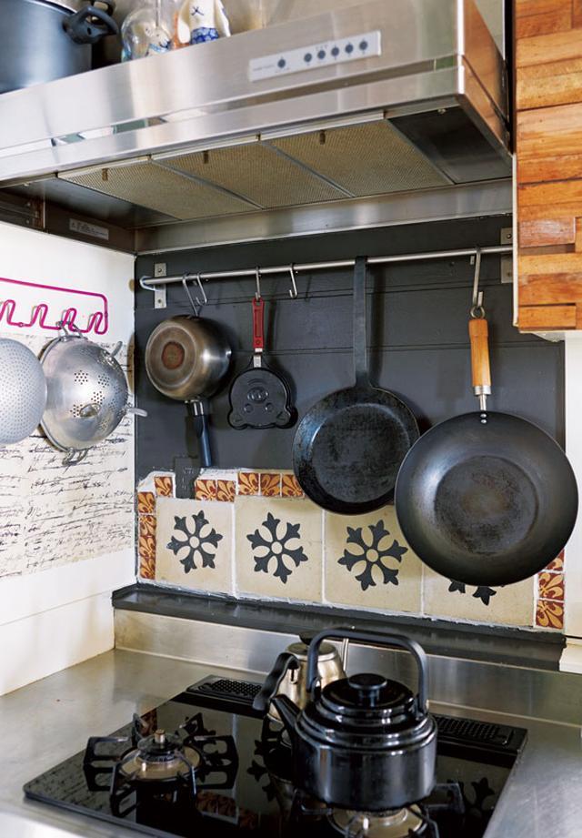 画像: 出番の多いフライパンや鍋などは、使いたいときにすぐ手が届くよう、コンロまわりに吊るして収納。ステンレス製のバーは「イケア」、壁は古いタイルで装飾し、DIYで設置した