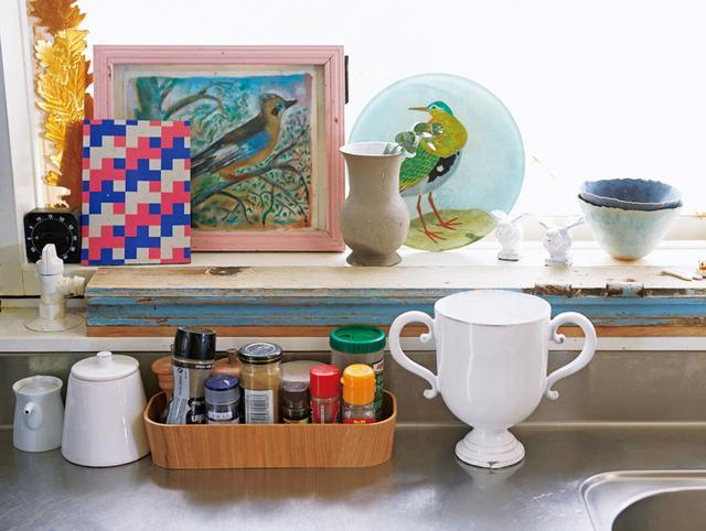 画像: 窓辺には、好きなお皿や絵などを飾って。「好きなものを出しておくと、料理するときも楽しいでしょう」。窓枠が細かったので、同じ高さの古いドア材を取り付けてスペースを広げている