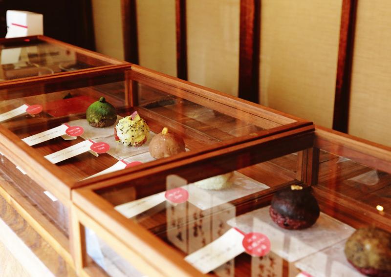 画像: 味わいのある木枠のケースには、色とりどりのおはぎのサンプルが並ぶ