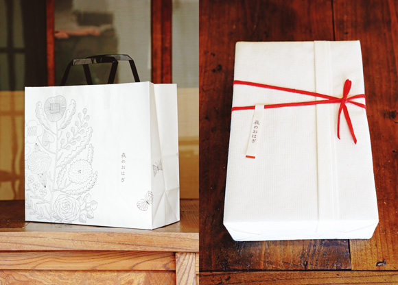 画像: 鹿児島睦さんデザインの紙袋もうれしい。贈答用には赤い帯付きの箱に詰めて(料金別途)