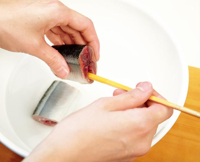画像: 薄い塩水の中で、割り箸で内臓を押し出して取り除く