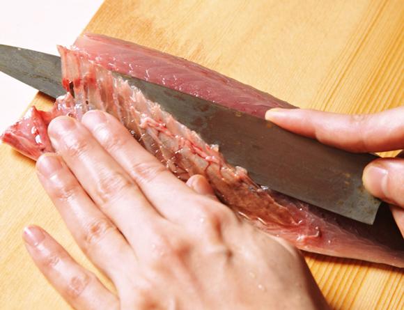 画像: 包丁をねかせて、腹骨をきれいにすき取る。端は刃を立てて落とす