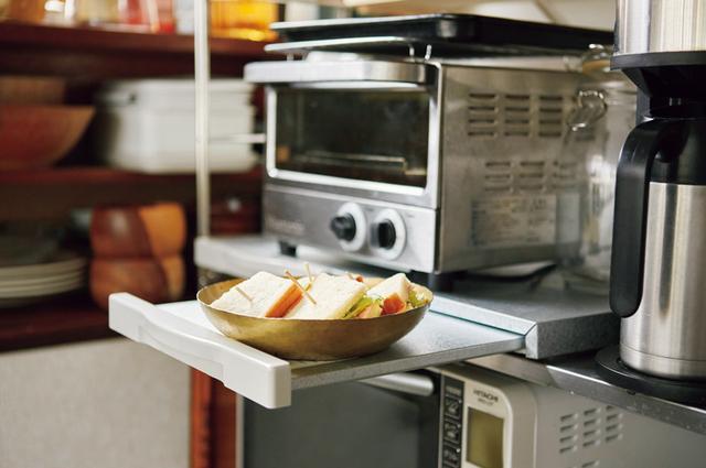 画像: オーブントースターの下には、通信販売で見つけたスライドテーブル付きの台を置いて。調理途中のものをちょっと置くのに重宝している