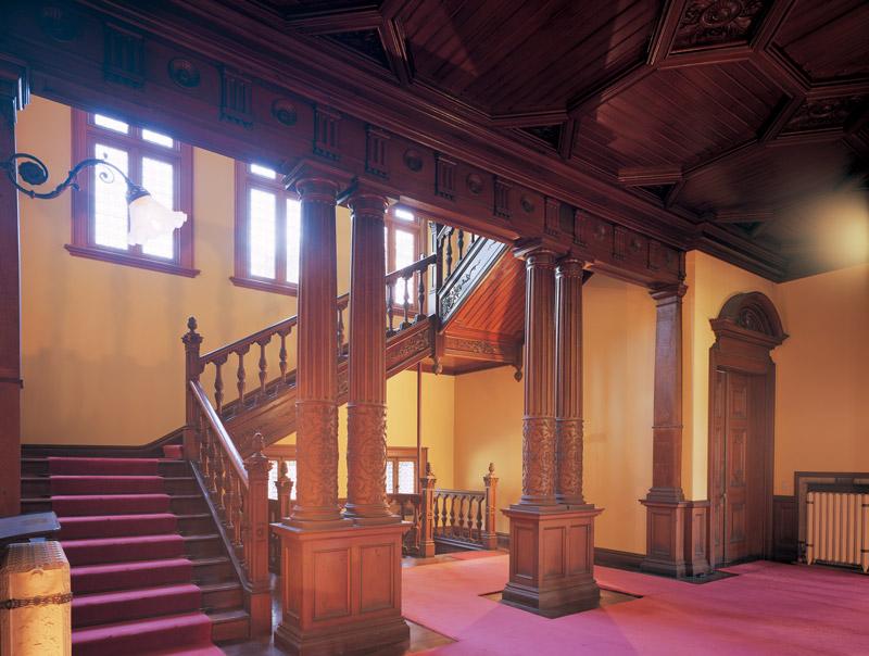 画像: 三つ折れの大階段へと続く玄関ホール。ペアコラム(双子柱)のジャコビアン様式の装飾が美しい