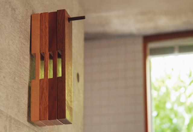 画像: 打ちっぱなしの壁の穴に、箸を利用したねじを自作して、かけている