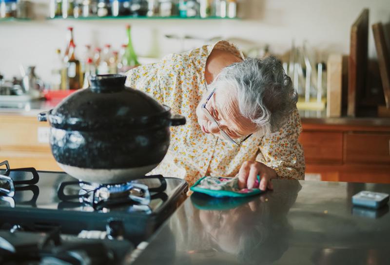 画像: 土鍋でごはんを炊くタミさん。目で見て、音を聴き、五感をすべて使って炊き上げていく。「台所のことは体で覚えて心を込めることです」という