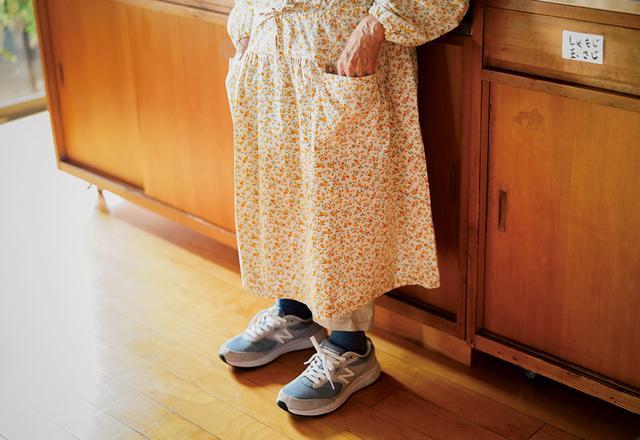 画像: 台所で着るかっぽう着は、生徒さんに縫ってもらったもの。「着心地が全然違う」。スニーカーは足の負担を減らすため。背も少し高くなるので仕事がしやすい