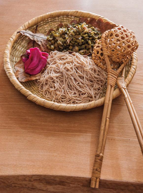 画像: 木曾から送られてくる伝統食・すんき漬けを使って、毎年すんきそば鍋を作ります。投汁籠(とうじかご)にそばを入れて投じ(温め)たら椀へ。酸味がおいしい一品。