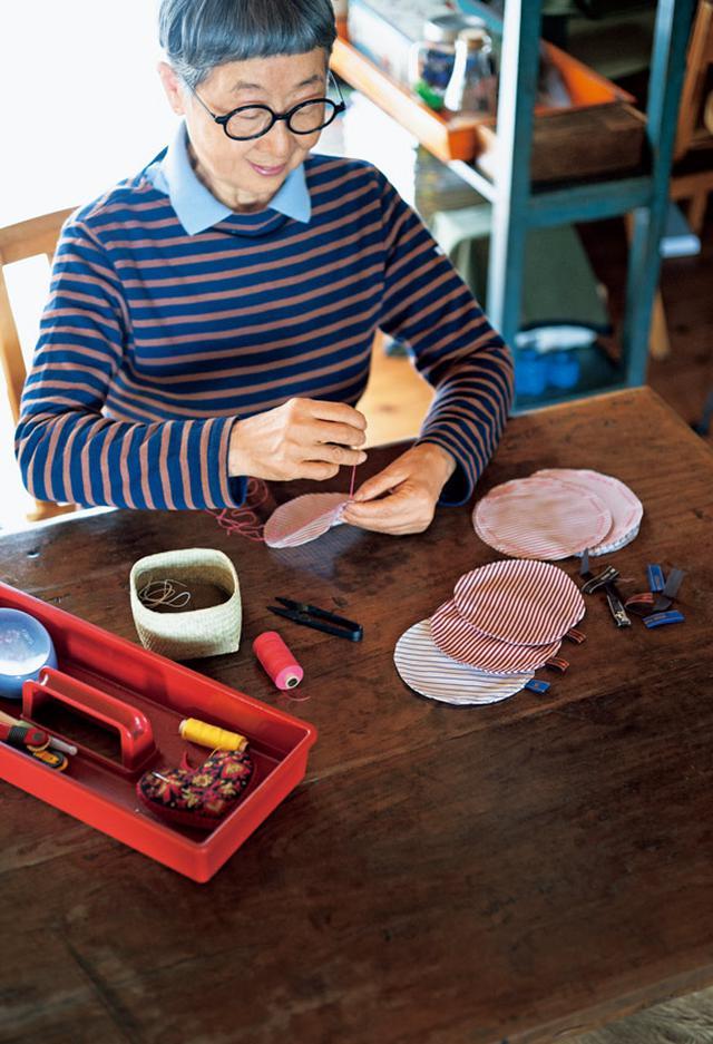 画像: お裁縫セットを広げてリビングのダイニングテーブルでコースターをつくる徳田さん。写真の右上に写っている棚の奥に、ミシンかけをする小さな洋裁スペースがある
