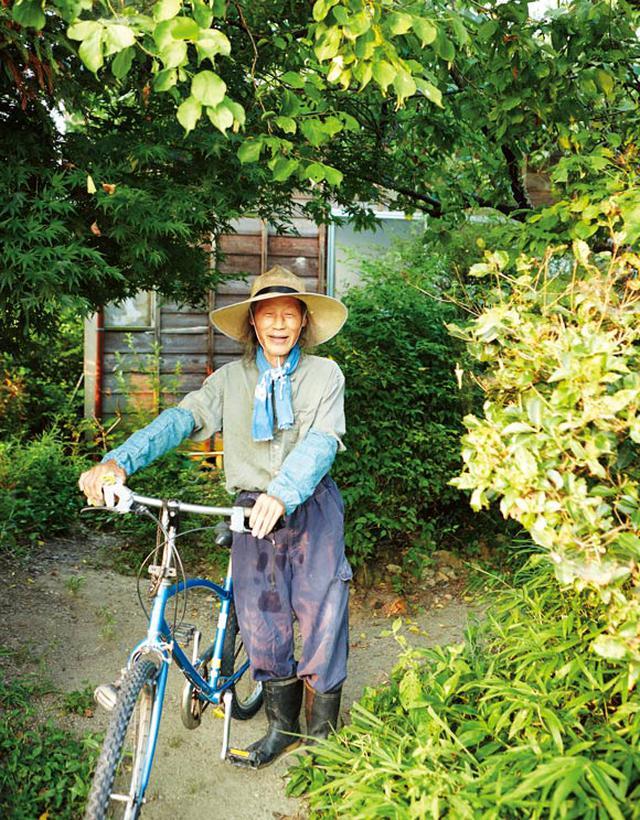 画像: 野良着スタイルの川口さん。木々や花が豊かな自宅の庭先で。車や機械類を持たない川口さんは、腰に鎌を差して、さっそうと自転車に乗って田んぼや畑へ向かう