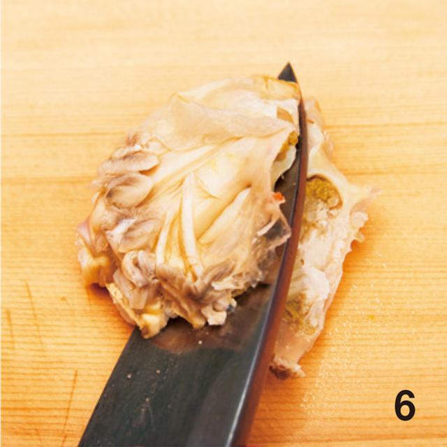 画像: 6 胴を割る。胴の真ん中から脚のあった方向に包丁を斜めに入れ、半分に割る