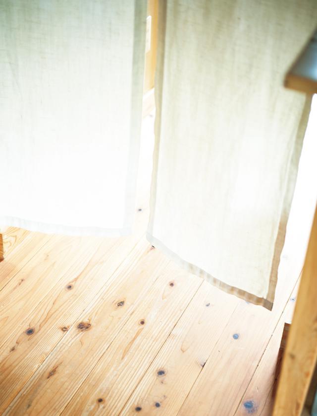画像: リビングダイニングと寝室・バスルームの境。上部に突っ張り棒を渡して自分でつくった仕切り布をかけて