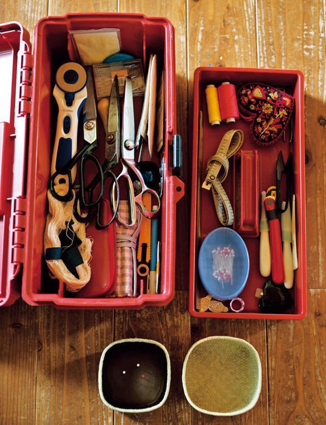 画像: 針や糸、はさみなど、よく使う裁縫道具は赤い工具箱に集約。「なにより、丈夫で収納力抜群。2段重ねで持ち手があるので、あっちこっち持っていくにも便利です」。手前の針刺しは小さなかごを使ってつくったもの。コーヒー豆の煎じカスが入っている