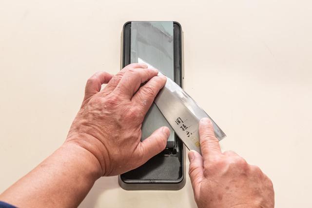 画像: 包丁を持つ手は、利き手の親指は峰に、人差し指は刃先の近くに添える。利き手でない方の指2本ほどを刃先の近くに添える