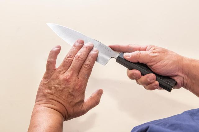 画像: バリを確認するときは、指3本ほどを使い、指先で刃の側面から刃先に向かいなでるようにする。指を切る恐れがあるので、刃先だけをなぞるような触れ方はしないこと
