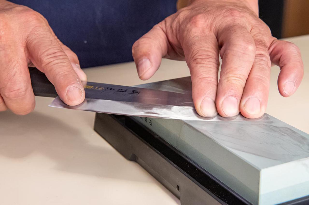 画像: 砥石に包丁を当てて研いでいく。こちら側は切刃がないので、角度をつけてはいけない