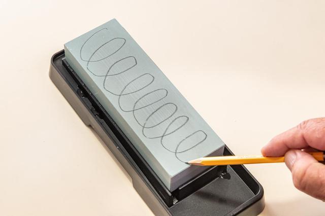 画像: 一度包丁を研ぐと砥石表面が平らではなくなる。平らに戻す目印として鉛筆で印をつける