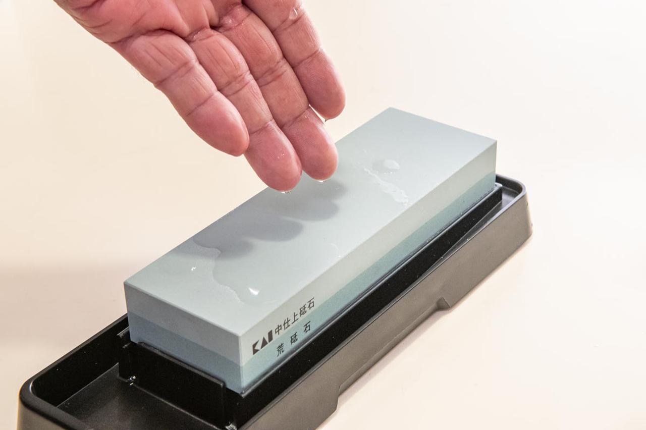 画像: 砥石が乾いて滑りが悪いと感じたら、指先から水をたらして砥石に水分を補給する