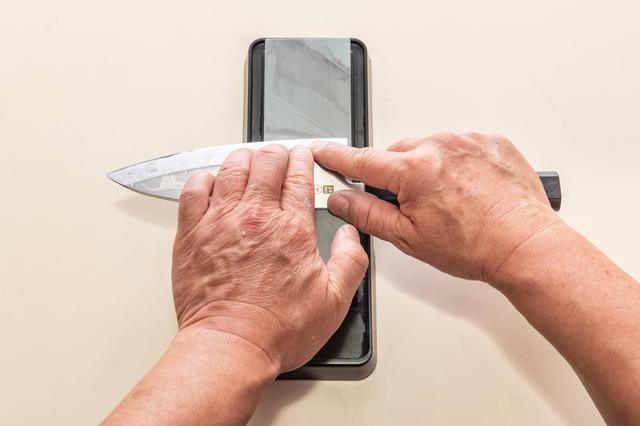 画像: あご近くを研ぐ際は、持ち手が砥石に当たらないように、包丁を砥石に対して直角に置く