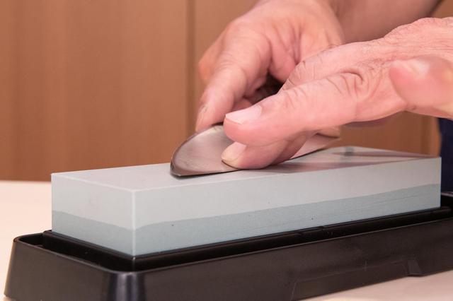 画像: 切刃を砥石に密着させる。この状態をキープして研ぐのが肝心