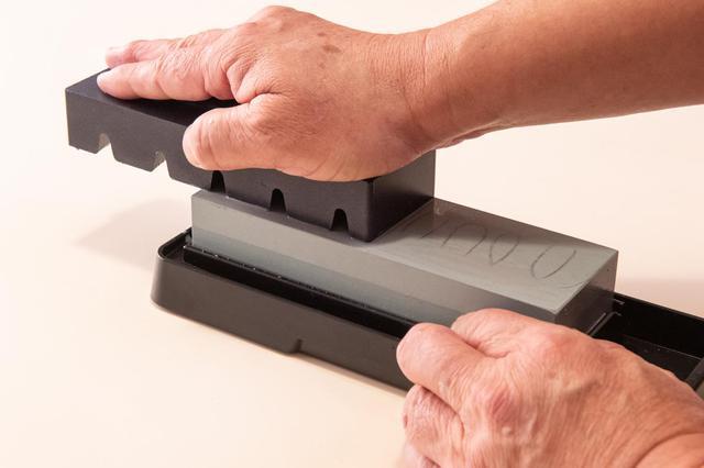 画像: 砥石は、砥石表面で平らに整える。洋包丁は1回研ぐごとに、和包丁は研いでいる最中に何回かこの作業を行うといい