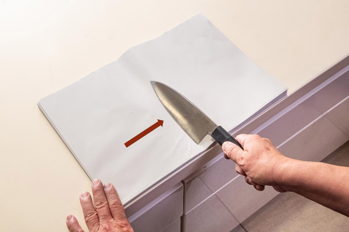 画像: 反対側の刃のバリも、同様に取る。最後は包丁を救い上げるように新聞紙から離すと、バリがよく取れる