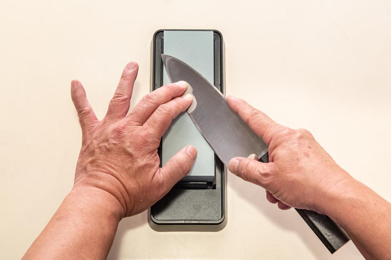 画像: 切れ刃を砥石に密着させ続けたまま、砥石の上を上下に動かすことで、刃が研がれていく