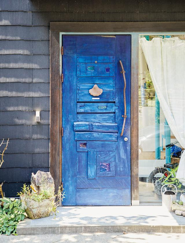 画像: 玄関ドアも、テーブルを手がけた中川さん作 家を建てるとき、玄関ドアはテーブルと同じ中川さんにつくってもらおうと決めていた。サーフィンが好きなご主人が、海が近い環境のことを考えて、深いブルーで仕上げてくれたそう