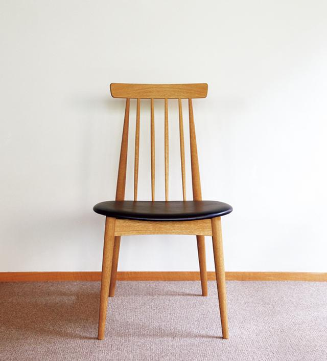 画像: 「スタンダードトレード」の「CHR-05A-L」 大きく傾斜した後脚に支えられる4本のスポークが背中にフィットする。「姿勢よく座れるの」と、かおりさん。浅いすり鉢状の座面はレザー張り。モダンな黒と木の組み合わせが、キリッとした印象