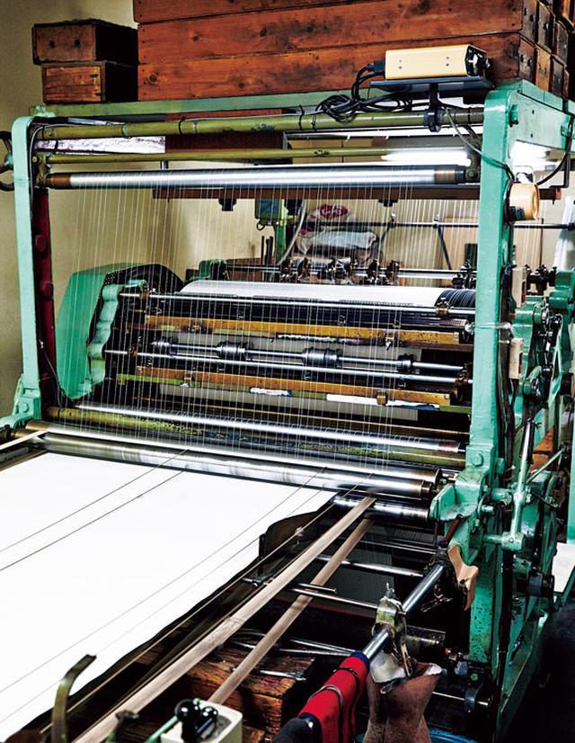 画像: 手前から紙が入り、S字を描くように機械の中を通過しながら両面に罫線が引かれる。ヒーター付きで、瞬時にインクが乾く。一方向しか引けないため、方眼の罫線を引く際は紙の向きを90度変え、再度、差し込む