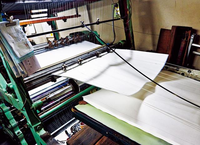 画像: 機械に張りめぐらされた細い糸の間を通り、紙が進んでいく仕組み
