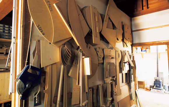 画像: 壁にかけられた、たくさんのパーツの型。「アリスファームから引き継いだものもありますね」。ちなみに、一番難しい工程は、椅子の脚や貫などを旋盤で削り出す作業だそう。「均一に仕上げるには、かなりの経験を要します」