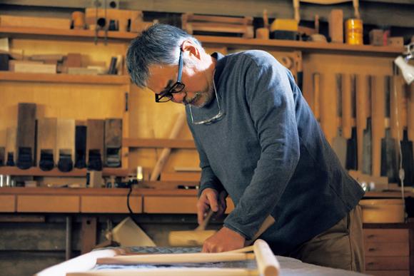 画像: 椅子の後脚に背板をはめ込む作業中の宇納さん