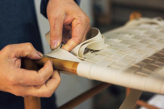 画像: 座面の混紡テープを編むさまは、見とれるほど鮮やか。座面にはクッション性をよくする薄い詰め物を採用