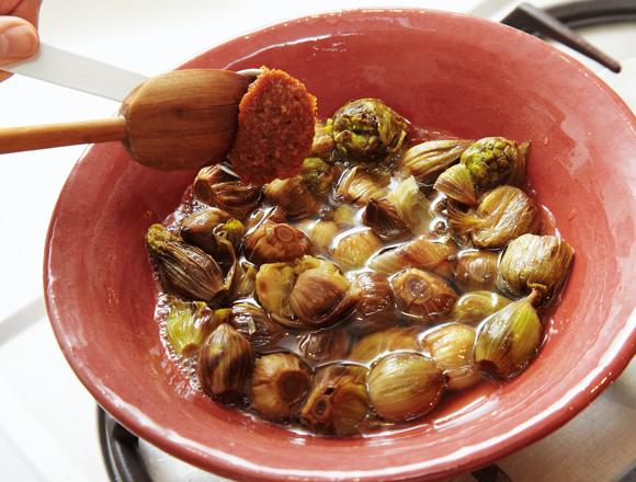 画像: 土鍋にふきのとうと水と酒を入れ、弱火で煮る。途中、砂糖を加え、混ぜながら煮る。酒が入ると黒ずむが、土鍋で煮ることで変色を防げる。