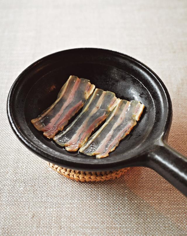 画像: 薄く切った干し豚を、熱したフライパンであぶる。脂が溶けかけてきたところを食べる