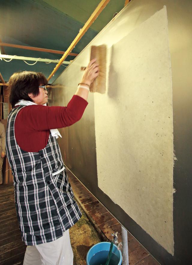 画像: 脱水した紙を熱い鉄板に張り付けて乾かす作業